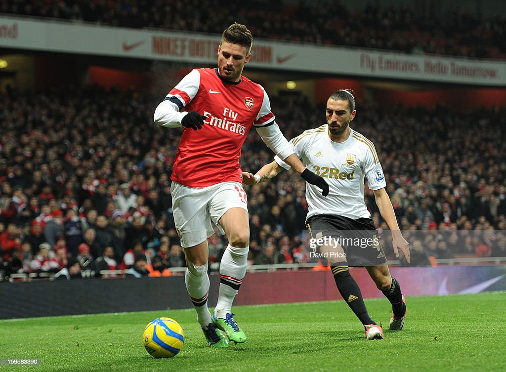 <a gi-track='captionPersonalityLinkClicked' href=/galleries/search?phrase=Olivier+Giroud&family=editorial&specificpeople=5678034 ng-click='$event.stopPropagation()'>Olivier Giroud</a> of Arsenal shields the ball from Chico Flores of Swansea during the FA Cup Third Round Replay match between Arsenal and Swansea City at the Emirates Stadium on January 16, 2013 in London, England.