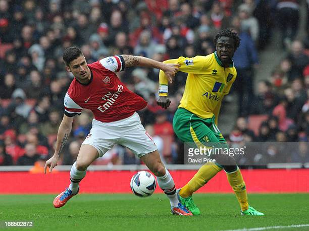 Olivier Giroud of Arsenal shields the ball from Kei Kamara of Norwich during the Barclays Premier League match between Arsenal and Norwich City at...
