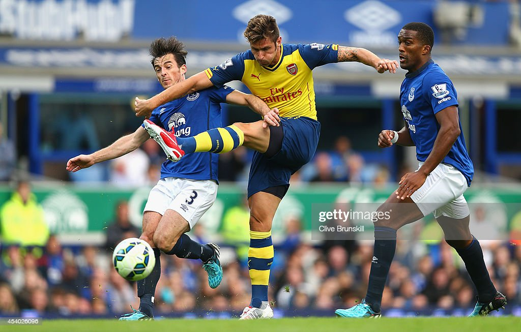 Olivier Giroud of Arsenal shoots at goal under pressure from Leighton Baines and Sylvain Distin of Everton during the Barclays Premier League match between Everton and Arsenal at Goodison Park on August 23, 2014 in Liverpool, England.