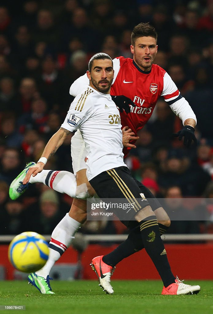 Olivier Giroud of Arsenal shoots past Chico Flores of Swansea City during the FA Cup with Budweiser Third Round Replay match between Arsenal and...