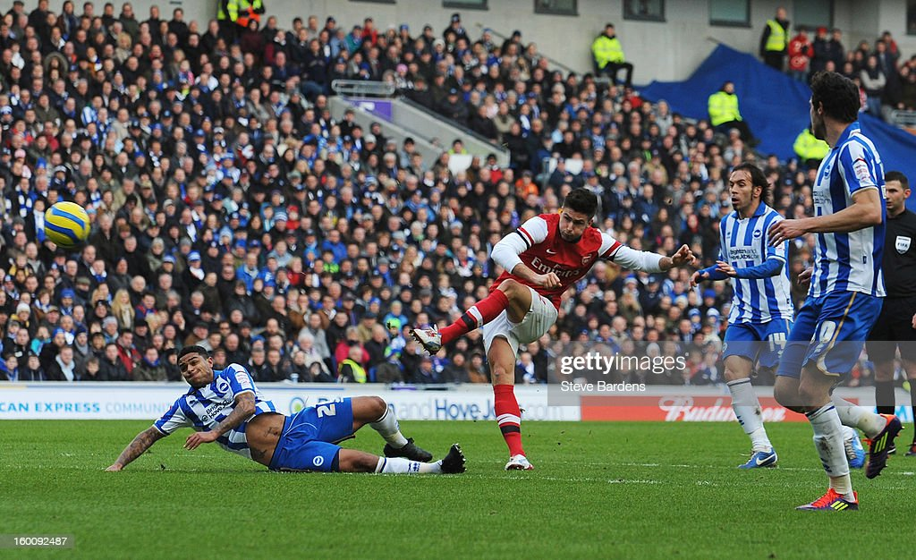 Olivier Giroud of Arsenal shoots past Liam Bridcutt of Brighton & Hove Albion to score their first goal during the FA Cup with Budweiser Fourth Round match between Brighton & Hove Albion and Arsenal at Amex Stadium on January 26, 2013 in Brighton, England.