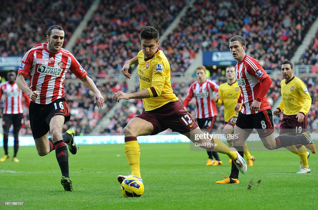 Olivier Giroud of Arsenal shoots under pressure from John O'Shea and Craig Gardner of Sunderland during the Barclays Premier League match between Sunderland and Arsenal at Stadium of Light on February 09, 2013 in Sunderland, England.