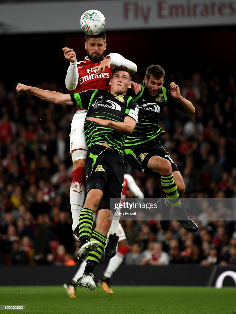 Olivier Giroud of Arsenal wins a header over Joe Wright of Doncaster Rovers and Matthew Blair of Doncaster Rovers during the Carabao Cup Third Round match between Arsenal and Doncaster Rovers at Emirates Stadium on September 20, 2017 in London, England.