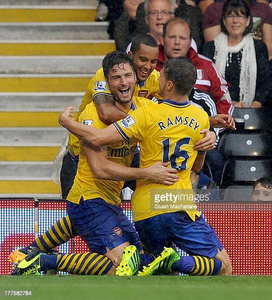 Olivier Giroud of Arsenel celebrates scoring the 1st goal with Theo Walcott and Aaron Ramsey during the Barclays Premier League match between Fulham...