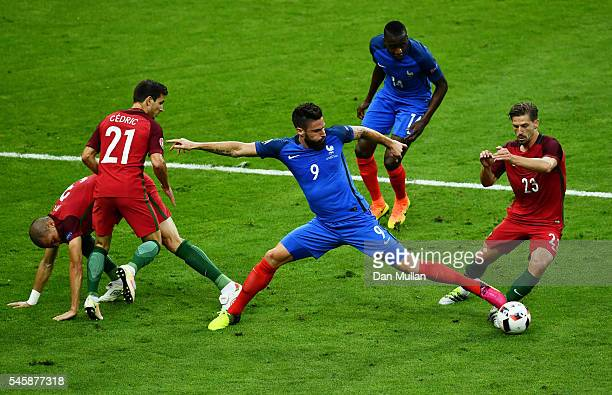 Olivier Giroud of France and Adrien Silva of Portugal compete for the ball during the UEFA EURO 2016 Final match between Portugal and France at Stade...