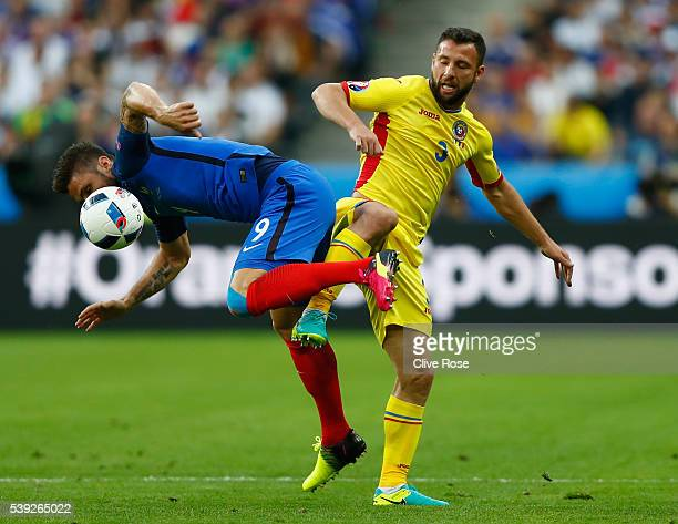 Olivier Giroud of France and Razvan Rat of Romania compete for the ball during the UEFA Euro 2016 Group A match between France and Romania at Stade...