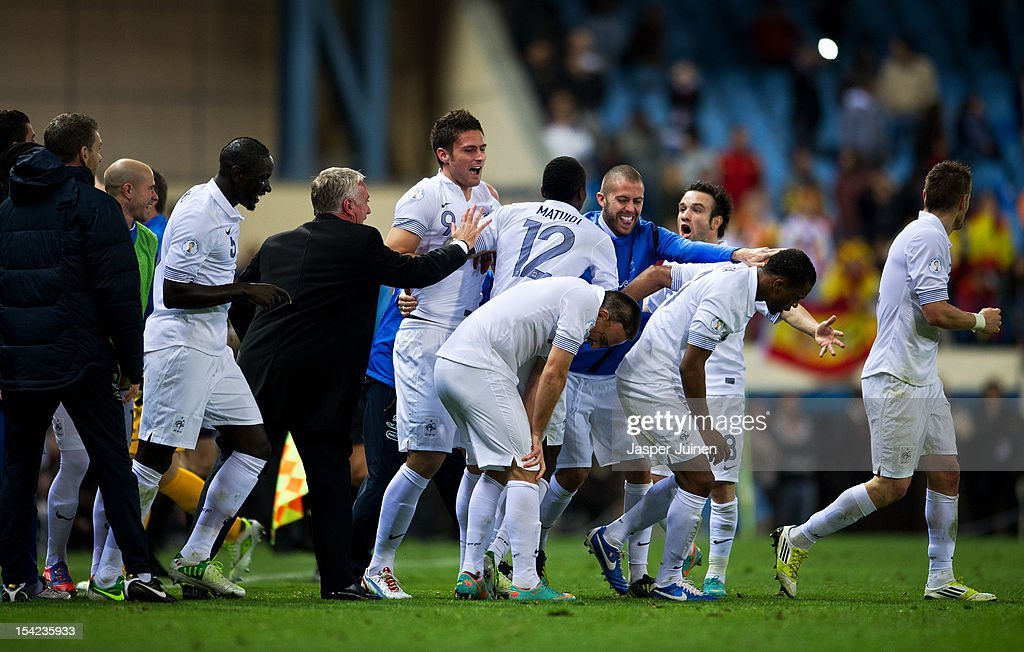 Olivier Giroud of France celebrates with his teammates and coach Didier Deschamps after scoring his sides last minute equalizing goal during the FIFA...