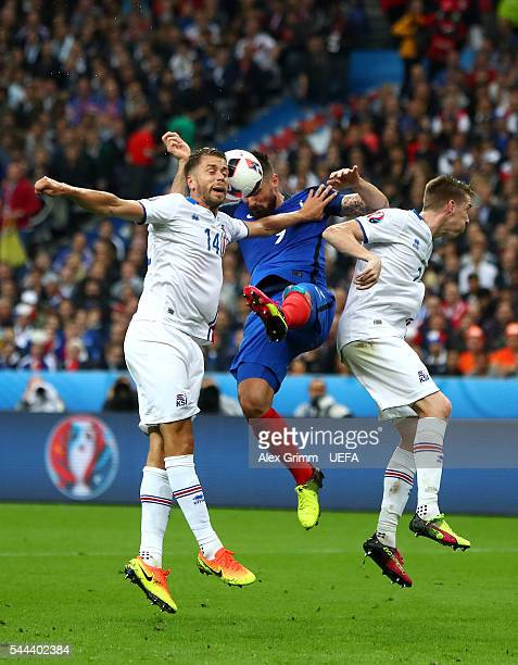 Olivier Giroud of France competes for the ball against Kari Arnason and Birkir Saevarsson of Iceland during the UEFA EURO 2016 quarter final match...