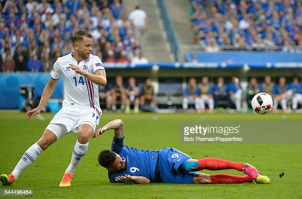 Olivier Giroud of France is tackled by Kari Arnason of Iceland during the UEFA EURO 2016 quarter final match between France and Iceland at Stade de...