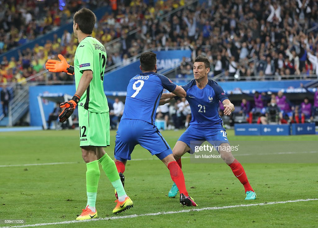Olivier Giroud of France watches his header go into the net to open the scoring as Laurent Koscielny of France reacts during the UEFA EURO 2016 Group A match between France and Romania at Stade de France on June 10, 2016 in Paris, France.