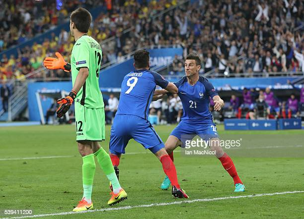 Olivier Giroud of France watches his header go into the net to open the scoring as Laurent Koscielny of France reacts during the UEFA EURO 2016 Group...
