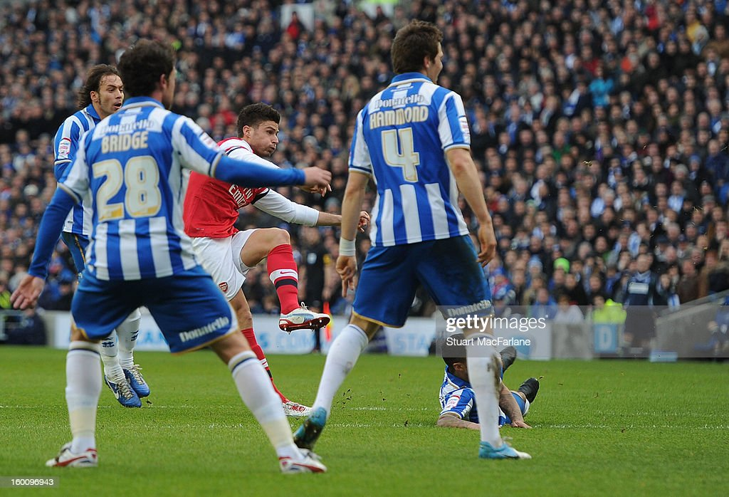 Olivier Giroud shoots past Brighton goalkeeper Casper Ankergren to score the 1st Arsenal goal during the FA Cup Fourth Round match between Brighton & Hove Albion and Arsenal at the Amex Stadium on January 26, 2013 in Brighton, England.