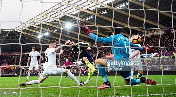 Olivier Giroud strokes in the first Arsenal goal past Lukasz Fabianski during the Premier League match between Swansea City and Arsenal at Liberty...