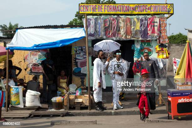 Olivier Kombe a Sapeur with his son outside one of their clothing shops on February 12 2017 in Kinshasa DRC The word Sapeur comes from SAPE a French...