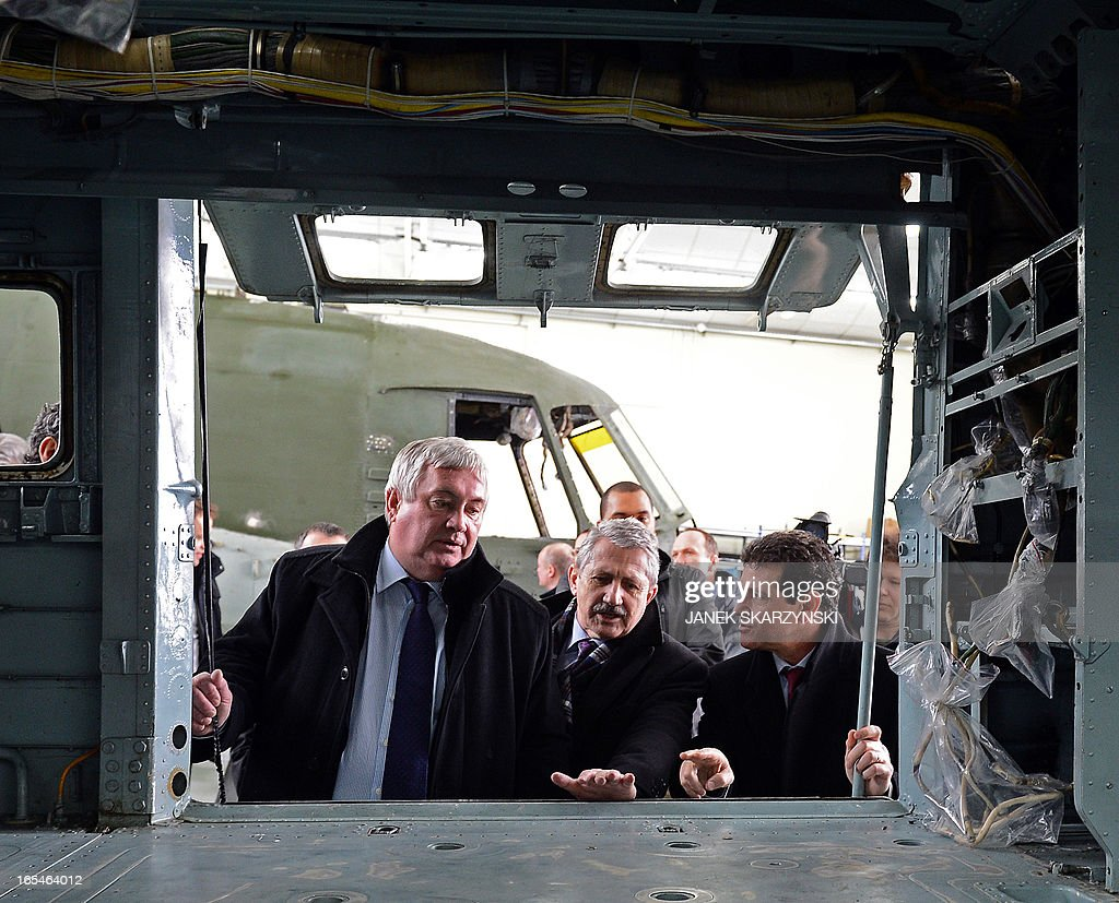 Olivier Lambert (L) and Joseph Saporito (R) Eurocopter vice-Presidents and Jan Pietowski (C), President of the Military Aviation Factory No1 in Lodz inspect a helicopter under construction after signing an agreement on April 4, 2013. Eurocopter, the largest helicopter manufacturer in the world, signed a contract with the Military Aviation Factory No1 in Lodz. The agreement is an order for 70 helicopters for the Polish Army.