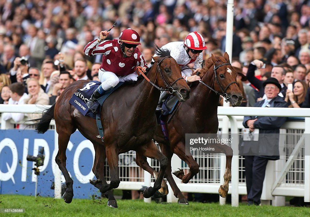 Olivier Peslier (L) riding Charm Spirit crosses the finish line ahead of Richard Hughes riding Night of the Thunder to win The Queen Elizabeth II Stakes at Ascot Racecourse on October 18, 2014 in Ascot, England.