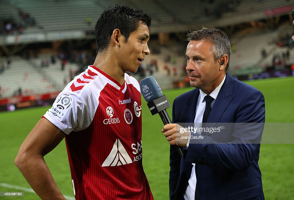 Olivier Tallaron of Canal Plus interviews Aissa Mandi of Reims after the French Ligue 1 match between Stade de Reims and Paris Saint Germain FC at the Stade Auguste Delaune on August 8, 2014 in Reims, France.