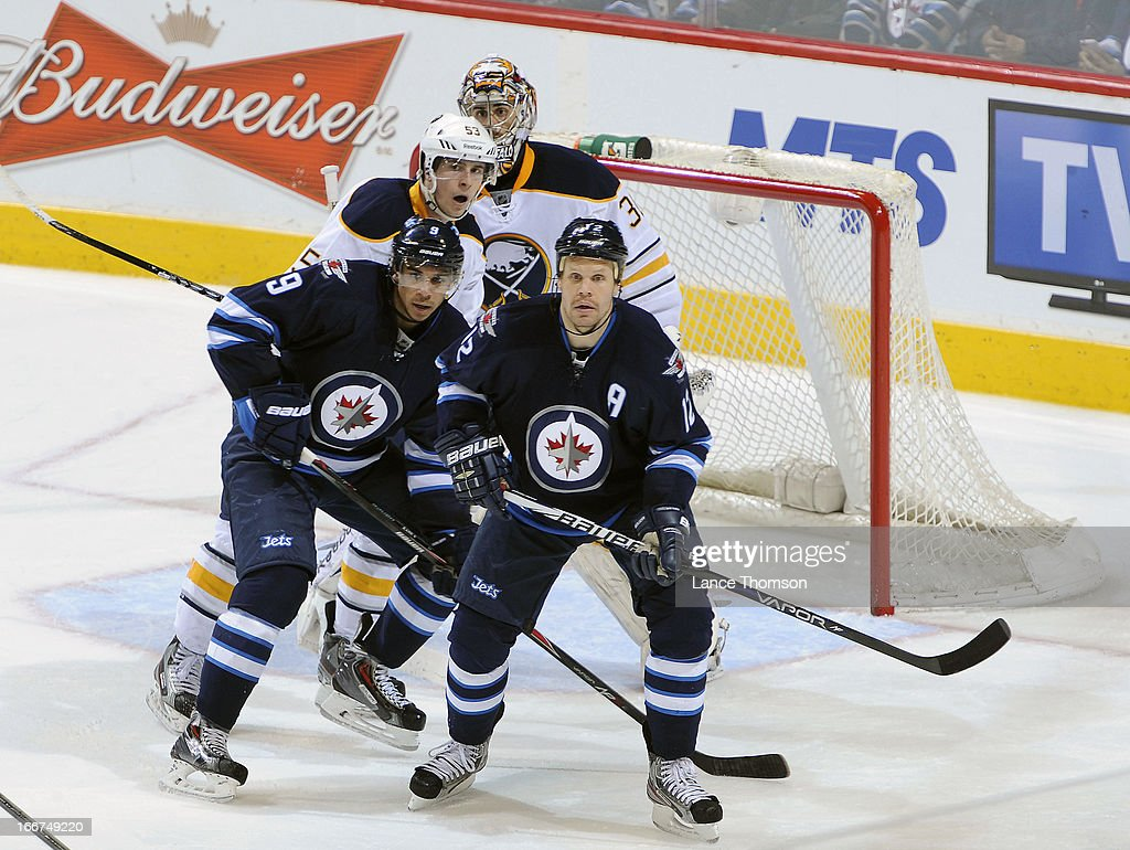 Olli Jokinen #12 and Evander Kane #9 of the Winnipeg Jets keep an eye on the play as they set a screen in front of Mark Pysyk #53 and goaltender Ryan Miller #30 of the Buffalo Sabres during second period action at the MTS Centre on April 9, 2013 in Winnipeg, Manitoba, Canada. The Jets defeated the Sabres 4-1.