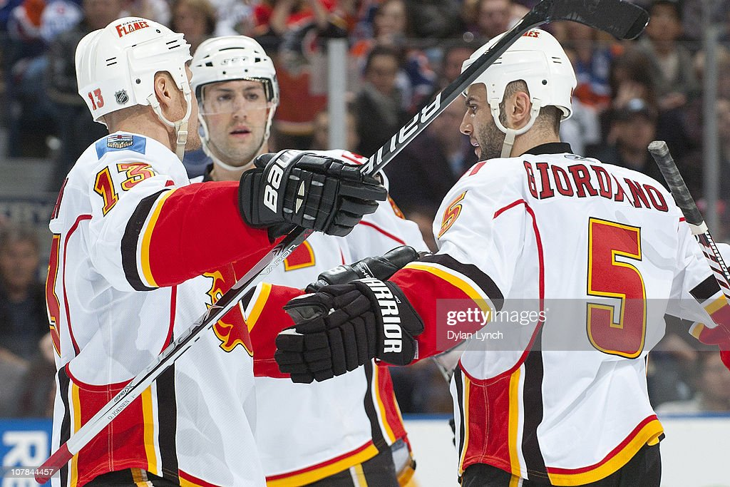 Olli Jokinen #13 and Mark Giordano #5 of the Calgary Flames celebrate a second period goal against the Edmonton Oilers at Rexall Place on January 1, 2011 in Edmonton, Alberta, Canada.