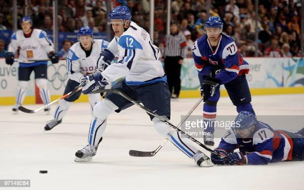 Olli Jokinen of Finland is challenged by Lubomir Visnovsky of Slovakia during the ice hockey men's bronze medal game between Finland and Slovakia on...
