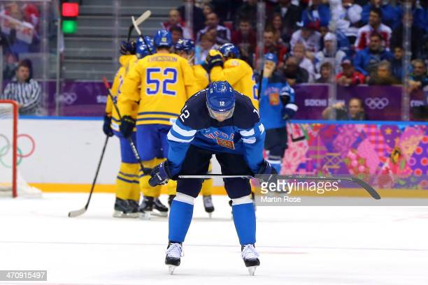 Olli Jokinen of Finland looks down as Sweden celebrate a goal by Loui Eriksson in the second period during the Men's Ice Hockey Semifinal Playoff on...
