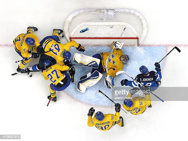 Olli Jokinen of Finland looks on as Henrik Lundqvist of Sweden lies in the creaseduring the Men's Ice Hockey Semifinal Playoff on Day 14 of the 2014...