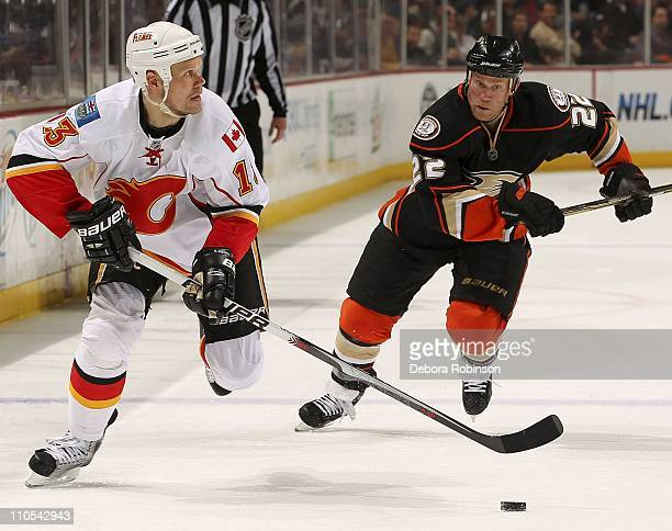 Olli Jokinen of the Calgary Flames controls the puck against Todd Marchant of the Anaheim Ducks during the game at Honda Center on March 20 2011 in...