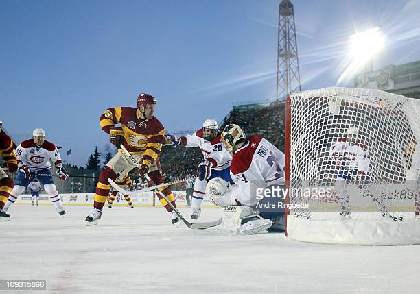 Olli Jokinen of the Calgary Flames is stopped by James Wisniewski and goaltender Carey Price of the Montreal Canadiens in second period action during...