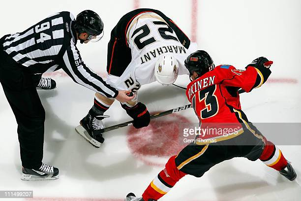 Olli Jokinen of the Calgary Flames takes a faceoff against Todd Marchant of the Anaheim Ducks on March 30 2011 at the Scotiabank Saddledome in...