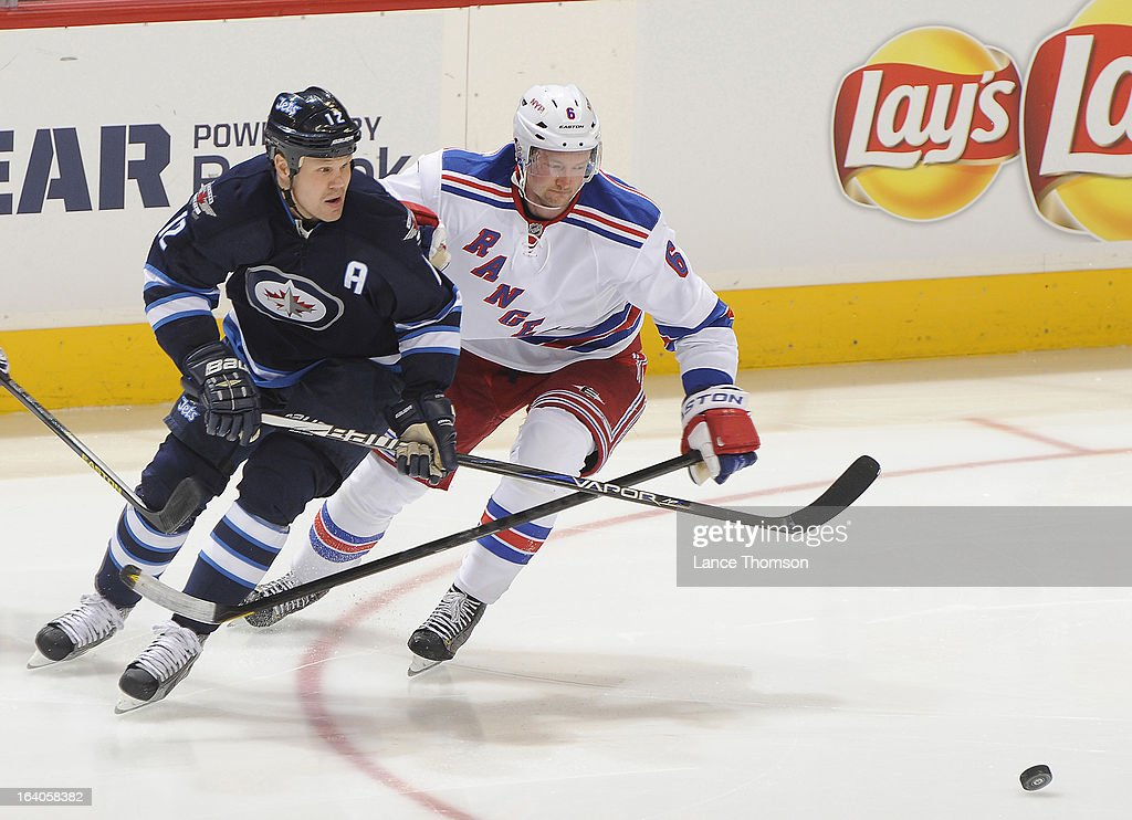 Olli Jokinen #12 of the Winnipeg Jets and Anton Stralman #6 of the New York Rangers chase after the loose puck during second period action at the MTS Centre on March 14, 2013 in Winnipeg, Manitoba, Canada. The Jets defeated the Rangers 3-1.