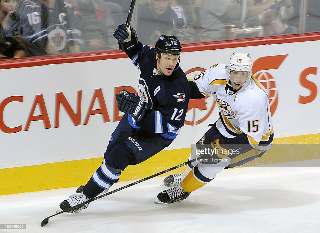 <a gi-track='captionPersonalityLinkClicked' href=/galleries/search?phrase=Olli+Jokinen&family=editorial&specificpeople=202946 ng-click='$event.stopPropagation()'>Olli Jokinen</a> #12 of the Winnipeg Jets and Craig Smith #15 of the Nashville Predators follow the play around the boards during second period action at the MTS Centre on October 20, 2013 in Winnipeg, Manitoba, Canada.