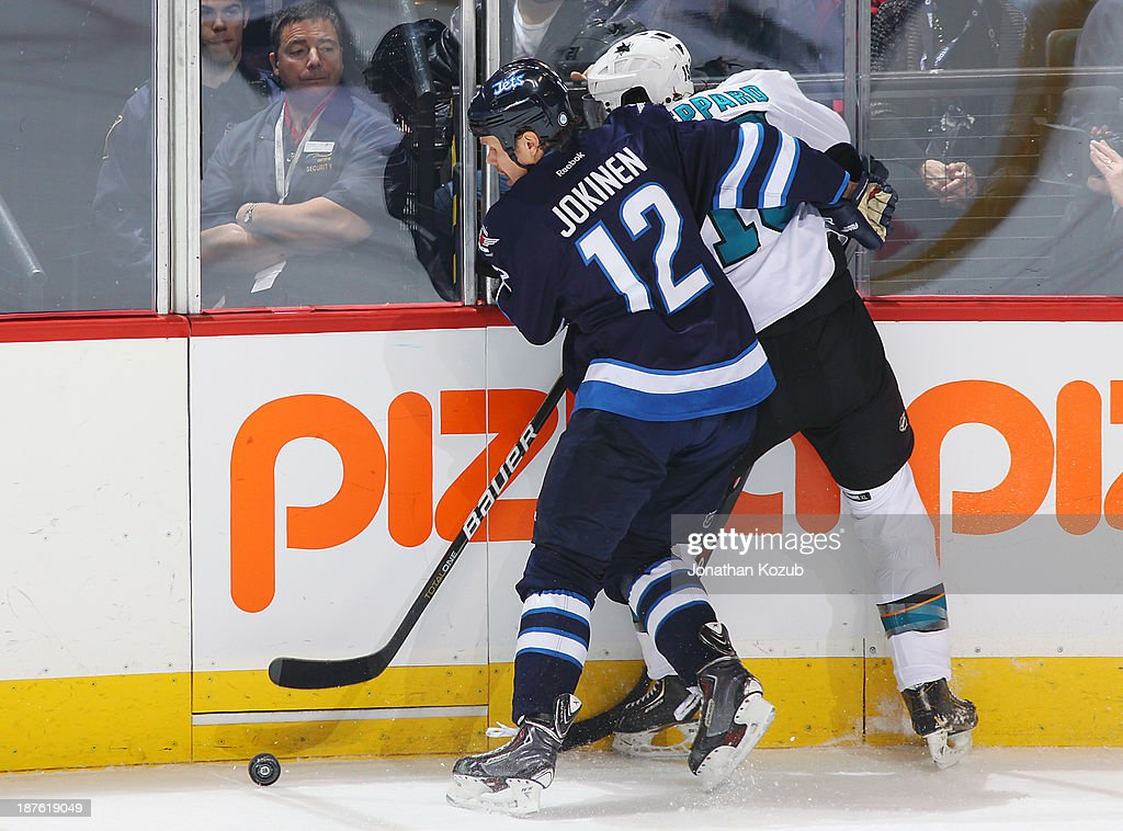 <a gi-track='captionPersonalityLinkClicked' href=/galleries/search?phrase=Olli+Jokinen&family=editorial&specificpeople=202946 ng-click='$event.stopPropagation()'>Olli Jokinen</a> #12 of the Winnipeg Jets checks James Shepard #15 of the San Jose Sharks along the boards during second period action at the MTS Centre on November 10, 2013 in Winnipeg, Manitoba, Canada.