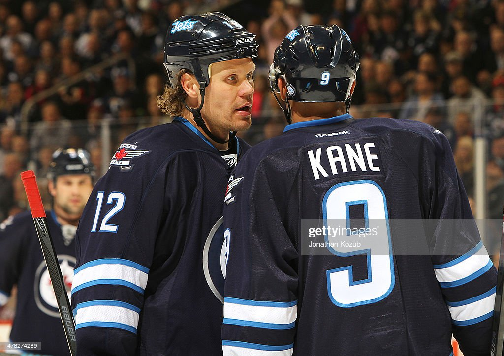 <a gi-track='captionPersonalityLinkClicked' href=/galleries/search?phrase=Olli+Jokinen&family=editorial&specificpeople=202946 ng-click='$event.stopPropagation()'>Olli Jokinen</a> #12 of the Winnipeg Jets discusses strategy with teammate <a gi-track='captionPersonalityLinkClicked' href=/galleries/search?phrase=Evander+Kane&family=editorial&specificpeople=4303789 ng-click='$event.stopPropagation()'>Evander Kane</a> #9 during a third period stoppage of play against the Vancouver Canucks at the MTS Centre on March 12, 2014 in Winnipeg, Manitoba, Canada.