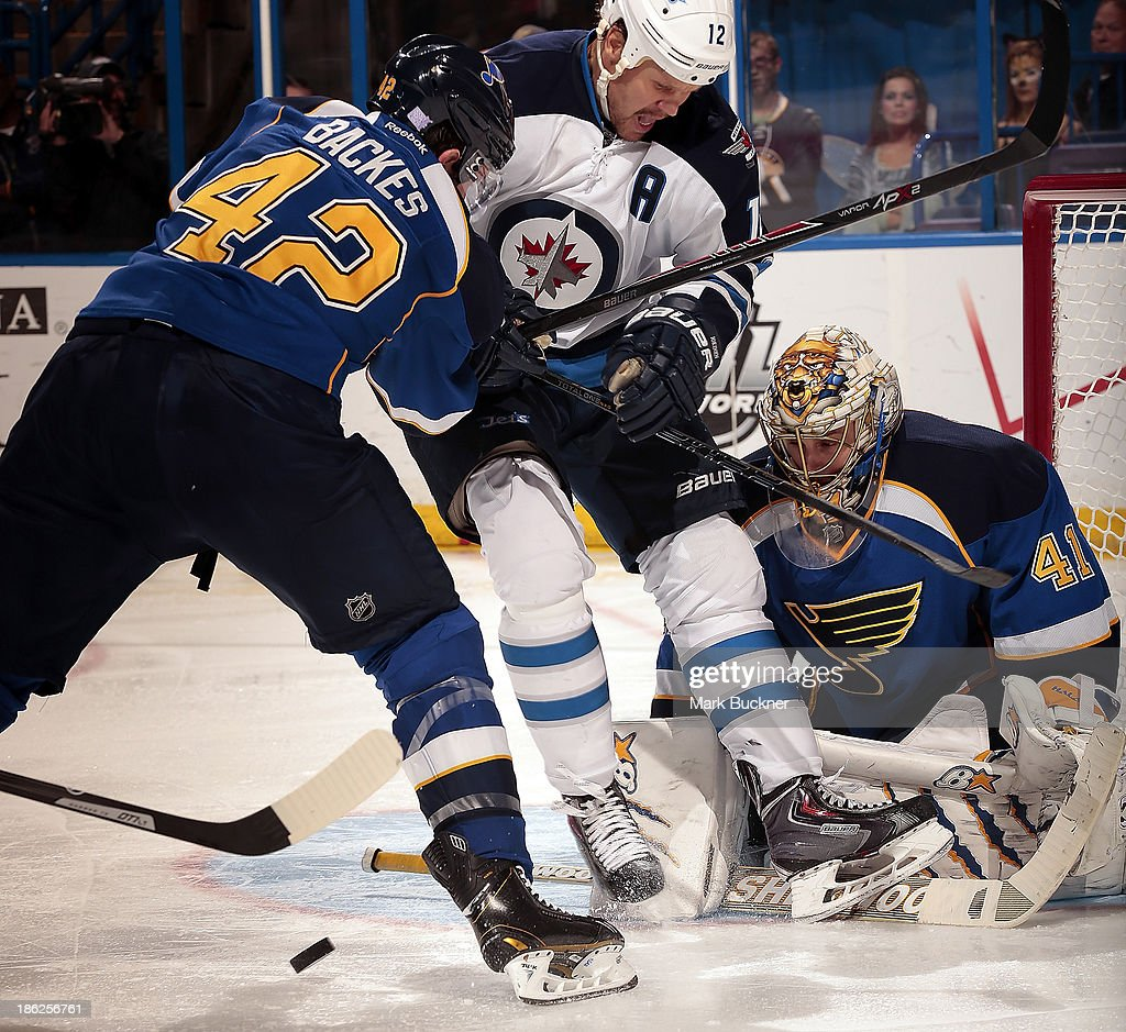 <a gi-track='captionPersonalityLinkClicked' href=/galleries/search?phrase=Olli+Jokinen&family=editorial&specificpeople=202946 ng-click='$event.stopPropagation()'>Olli Jokinen</a> #12 of the Winnipeg Jets gets sandwiched between <a gi-track='captionPersonalityLinkClicked' href=/galleries/search?phrase=David+Backes&family=editorial&specificpeople=2538492 ng-click='$event.stopPropagation()'>David Backes</a> #42 and <a gi-track='captionPersonalityLinkClicked' href=/galleries/search?phrase=Jaroslav+Halak&family=editorial&specificpeople=2285591 ng-click='$event.stopPropagation()'>Jaroslav Halak</a> #41of the St. Louis Blues on October 29, 2013 at Scottrade Center in St. Louis, Missouri.
