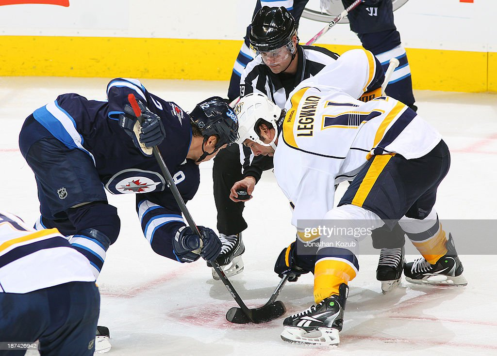 <a gi-track='captionPersonalityLinkClicked' href=/galleries/search?phrase=Olli+Jokinen&family=editorial&specificpeople=202946 ng-click='$event.stopPropagation()'>Olli Jokinen</a> #12 of the Winnipeg Jets gets set for a third period face-off against <a gi-track='captionPersonalityLinkClicked' href=/galleries/search?phrase=David+Legwand&family=editorial&specificpeople=202553 ng-click='$event.stopPropagation()'>David Legwand</a> #11 of the Nashville Predators at the MTS Centre on November 8, 2013 in Winnipeg, Manitoba, Canada.