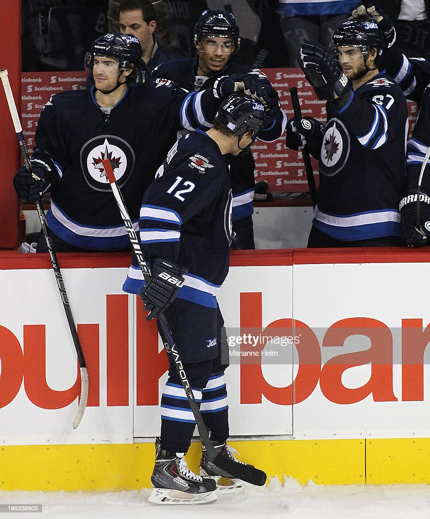 Olli Jokinen #12 of the Winnipeg Jets is greeted at the bench by teammates (L-R) Jim Slater #19, Evander Kane #9 and Michael Frolik #67 after scoring a goal against the St. Louis Blues in shootout action of an NHL game at the MTS Centre on October 18, 2013 in Winnipeg, Manitoba, Canada.