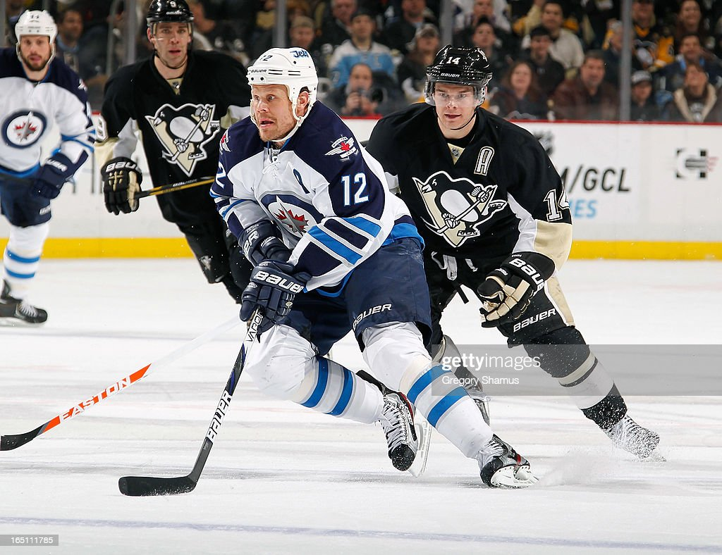 Olli Jokinen #12 of the Winnipeg Jets moves the puck up ice in front of Chris Kunitz #14 of the Pittsburgh Penguins on March 28, 2013 at Consol Energy Center in Pittsburgh, Pennsylvania.