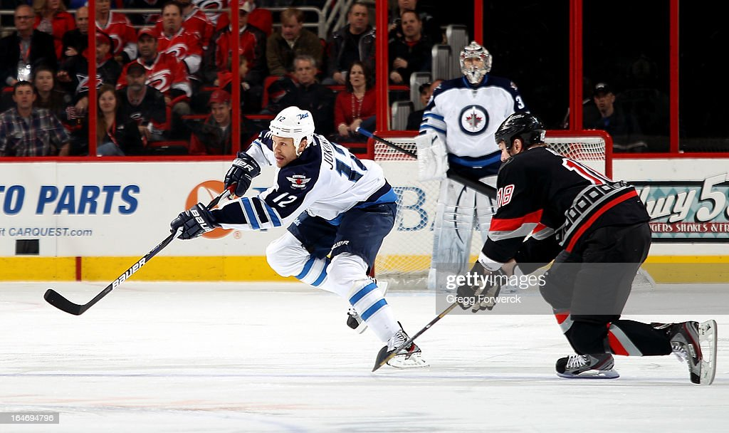 Olli Jokinen #12 of the Winnipeg Jets passes the puck as Adam Hall #18 of the Carolina Hurricanes moves in to defend during their NHL game at PNC Arena on March 26, 2013 in Raleigh, North Carolina.