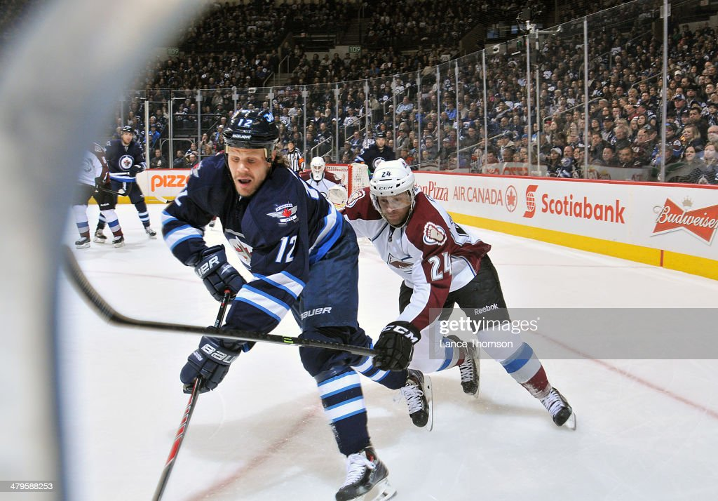 <a gi-track='captionPersonalityLinkClicked' href=/galleries/search?phrase=Olli+Jokinen&family=editorial&specificpeople=202946 ng-click='$event.stopPropagation()'>Olli Jokinen</a> #12 of the Winnipeg Jets plays the puck along the boards as Marc-Andre Cliche #24 of the Colorado Avalanche defends during first-period action at the MTS Centre on March 19, 2014 in Winnipeg, Manitoba, Canada.