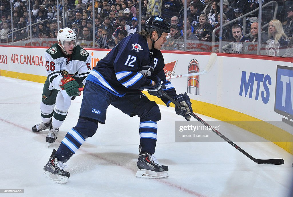 Olli Jokinen #12 of the Winnipeg Jets plays the puck along the boards as Erik Haula #56 of the Minnesota Wild defends during first period action at the MTS Centre on April 7, 2014 in Winnipeg, Manitoba, Canada. The Wild defeated the Jets 1-0.