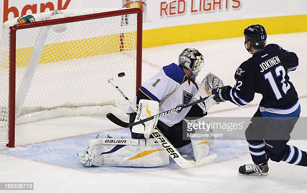 Olli Jokinen of the Winnipeg Jets scores the winning goal against Brian Elliott of the St Louis Blues in shootout action of an NHL game at the MTS...