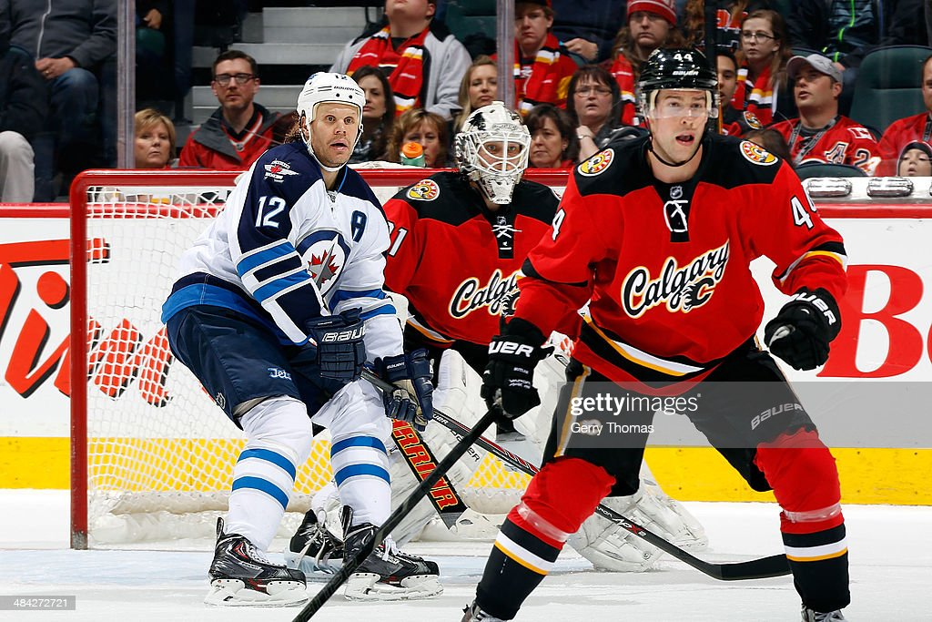 Olli Jokinen #12 of the Winnipeg Jets skates against Chris Butler #44 and Karri Ramo #31 of the Calgary Flames at Scotiabank Saddledome on April 11, 2014 in Calgary, Alberta, Canada.