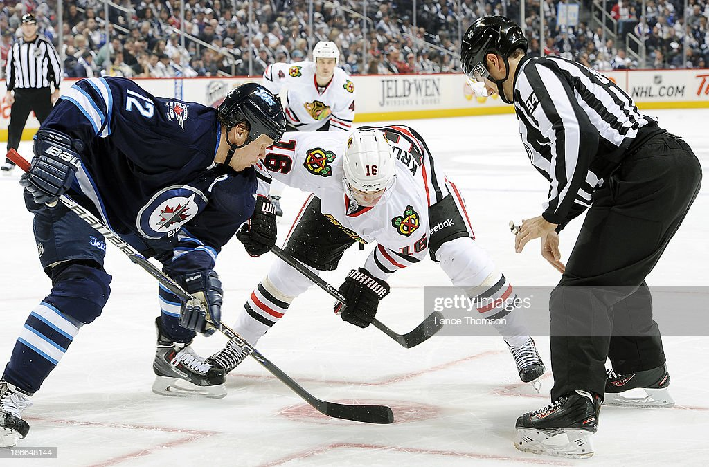 Olli Jokinen #12 of the Winnipeg Jets takes a third period face-off against Marcus Kruger #16 of the Chicago Blackhawks at the MTS Centre on November 2, 2013 in Winnipeg, Manitoba, Canada.