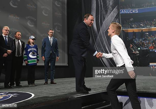 Olli Juolevi shakes the hand of NHL Commissioner Gary Bettman after being selected fifth overall by the Vancouver Canucks during round one of the...