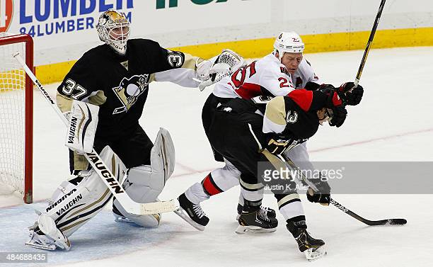 Olli Maatta of the Pittsburgh Penguins and Chris Neil of the Ottawa Senators battle in front of Penguins goalie Jeff Zatkoff during the game at...