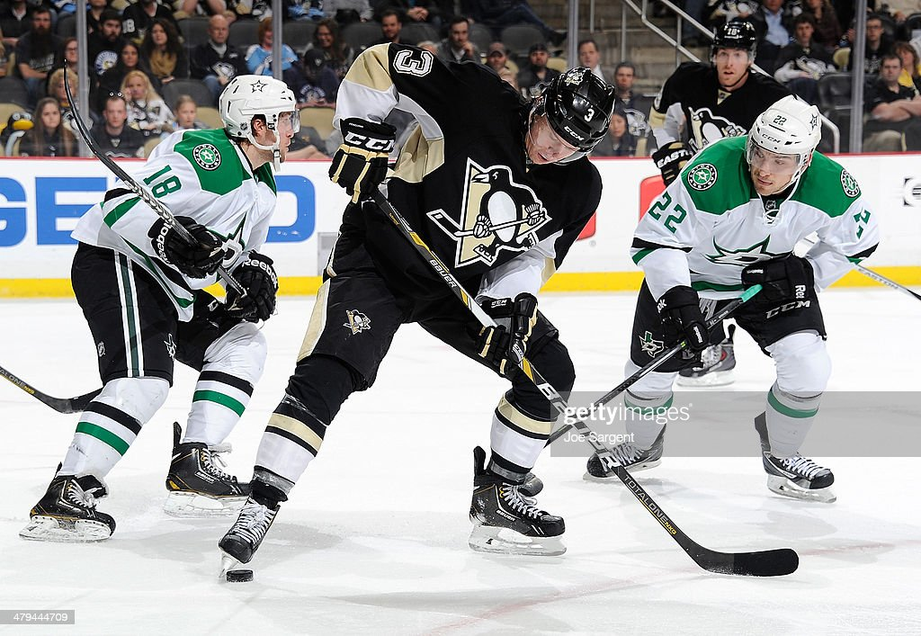 Olli Maatta of the Pittsburgh Penguins kicks the loose puck in front of Chris Mueller and Colton Sceviour of the Dallas Stars on March 18 2014 at...