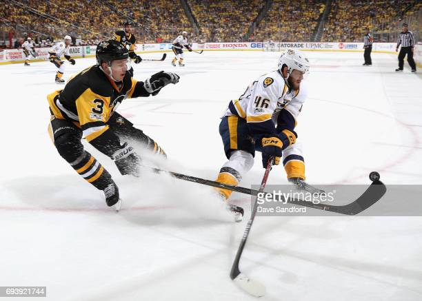 Olli Maatta of the Pittsburgh Penguins tips the puck away from Pontus Aberg of the Nashville Predators during the first period of Game Five of the...