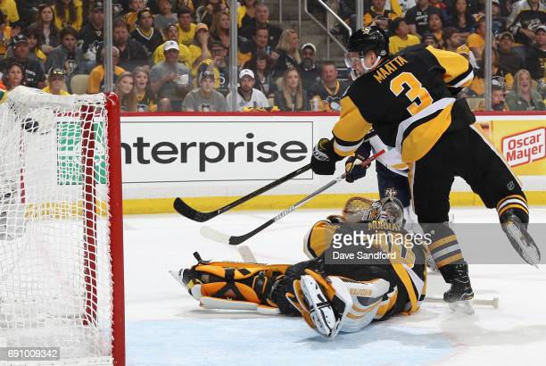 Olli Maatta of the Pittsburgh Penguins watches the puck over past goaltender Matt Murray on a shot by Pontus Aberg of the Nashville Predators during...
