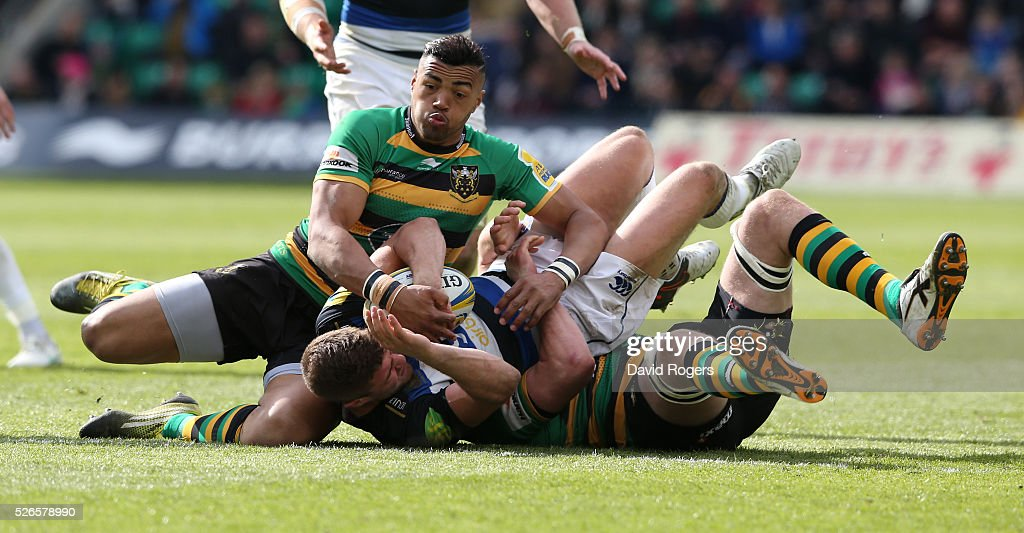 Ollie Devoto of Bath is held by Jamie Gibson and <a gi-track='captionPersonalityLinkClicked' href=/galleries/search?phrase=Luther+Burrell&family=editorial&specificpeople=871965 ng-click='$event.stopPropagation()'>Luther Burrell</a> during the Aviva Premiership match between Northampton Saints and Bath at Franklin's Gardens on April 30, 2016 in Northampton, England.