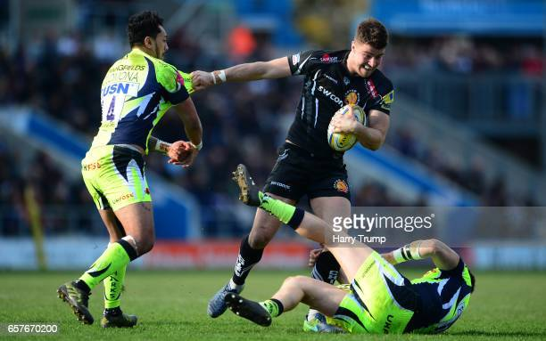 Ollie Devoto of Exeter Chiefs is tackled by Denny Solomona of Sale Sharks and Sam James of Sale Sharks during the Aviva Premiership match between...